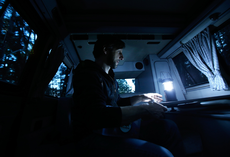 Dave Massie sets up an LED lantern that was provided by Peace Vans in the back of a 1991 Volkswagon Vanagon Westfalia at Camano Island State Park, Friday, April 1, 2016.