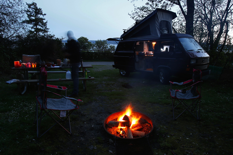 Campers make dinner as the sun sets over the Puget Sound at Camano Island State Park, Friday, April 1, 2016. The group of friends rented the 1991 Volkswagon Vanagon Westfalia from Peace Vans, and local van rental outfitter, located in the SODO neighborhood in Seattle.